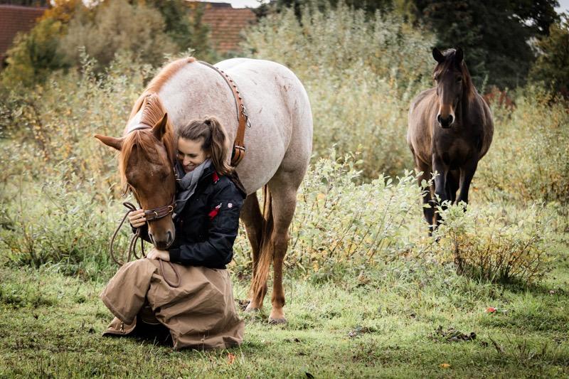 Petra sitzt in Hocke auf der Weide, Carey schnuppert an ihrer Hand